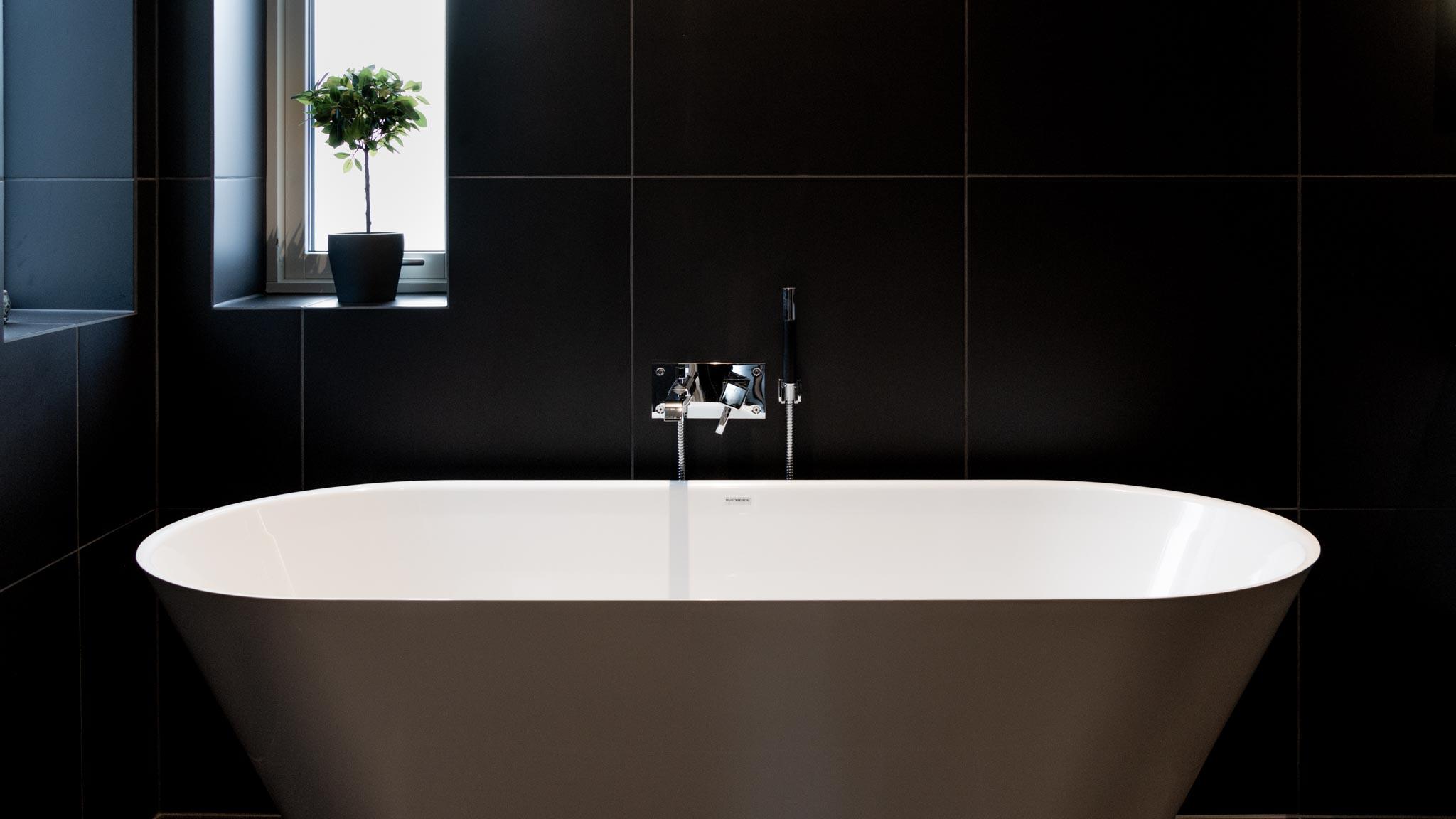 Sorte fliser og et stilfullt hvitt badekar ved vinduene